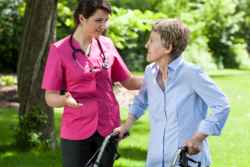 Old woman walking together with her nurse